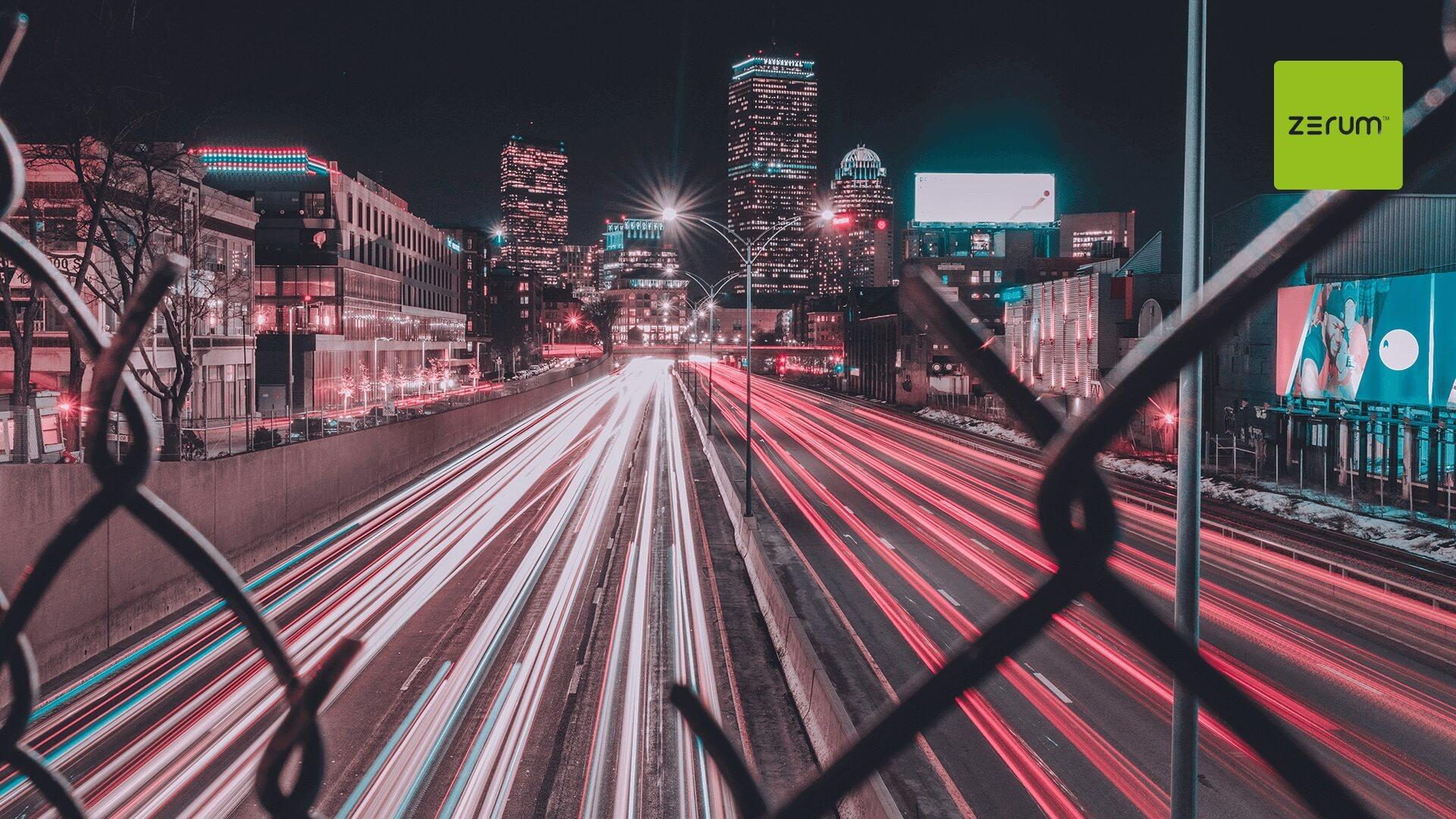 Fotografia de uma avenida vista através de uma cerca de arame -